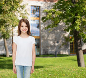 Smiling little girl in white blank t-shirt. Advertising, leisure, summer vacation, childhood and people - smiling little girl in white blank t-shirt over campus Stock Image