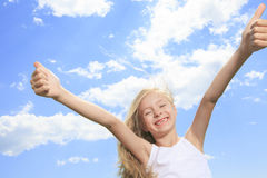 A smiling little girl in white blank t-shirt. A smiling thumb up little girl in white blank t-shirt showing thumbs up over blue sky background Stock Photo