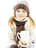 Smiling little girl with a white cup of hot drink. Royalty Free Stock Image