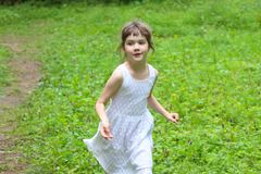 Smiling little girl in white dress runs at summer day. In park Stock Photo
