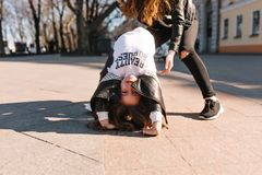 Smiling little girl in white shirt and leather jacket lying on the ground, playing with mother in trendy sneakers. Portrait of funny young mom and her playful stock photos