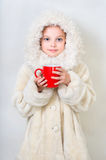 Smiling little girl in winter clothes with a red cup of hot drin Royalty Free Stock Image