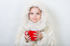 Smiling little girl in winter clothes with a red cup of hot drin Stock Photo