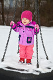 Smiling little girl on winter seesaw Royalty Free Stock Image