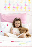 Smiling little girl writing in bed Stock Photos