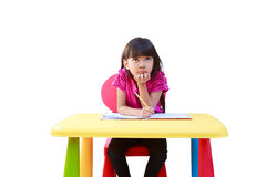 Smiling little girl writing on the desk Stock Photos