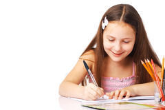 Smiling Little Girl Writing Something. Cute little girl writing something in the copybook and smiling Royalty Free Stock Photos
