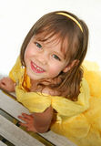 Smiling little girl in yellow dress. A smiling little girl is photographed by a bench in the summertime. She wears a yellow princess dress Stock Image