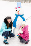 Smiling little girl and young woman with snowman in winter day Stock Photos