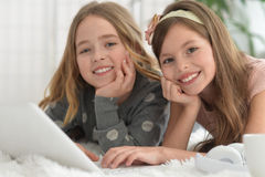 Smiling little girls using a laptop Royalty Free Stock Photos
