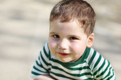Smiling little handsome boy looks at camera in park Stock Images