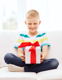 Smiling little holding gift box sitting on couch Stock Photography