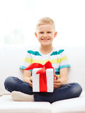 Smiling little holding gift box sitting on couch Royalty Free Stock Images