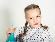 Smiling little housewife washed the window with a cloth and detergent. Large glass in foam. Housework concept. Smiling little housewife washed the window with a Royalty Free Stock Images