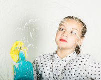 Smiling little housewife washed the window with a cloth and detergent. Large glass in foam. Housework concept. Smiling little housewife washed the window with a Stock Image