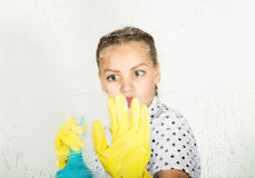 Smiling little housewife washed the window with a cloth and detergent. Large glass in foam. Housework concept. Smiling little housewife washed the window with a Royalty Free Stock Image
