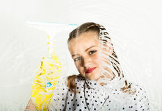 Smiling little housewife washed the window with a cloth and detergent. Large glass in foam. Housework concept. Smiling little housewife washed the window with a Stock Photography