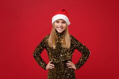 Smiling little kid girl 12-13 years old in glitter party outfit, Santa hat  on red background. New Year 2020