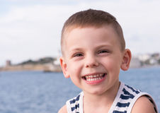 Smiling little kid in sailor stripes singlet on sea background Royalty Free Stock Photos