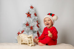 Smiling little kid sitting by Christmas tree, studio shot Royalty Free Stock Image