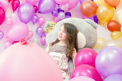 Smiling little lady posing lying on big teddy bear Royalty Free Stock Images