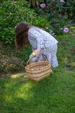 Smiling little latina girl in garden in Spring dress with Basket. In the Spring or Summer royalty free stock image