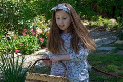 Smiling little latina girl in garden in Spring dress with Basket royalty free stock photography