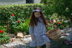 Smiling little latina girl in garden in Spring dress with Basket. In the Spring or Summer royalty free stock photos