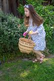 Smiling little latina girl in garden in Spring dress with Basket. In the Spring or Summer stock images