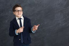Smiling little man in suit point away. Confident smiling little man in suit point away, black studio background, copy space royalty free stock photo