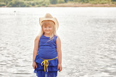 Smiling little model posing by lake Stock Images