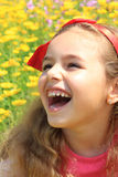 Smiling little pretty girl in a yellow flowers. Red bow-knots on. The curly hair Stock Images
