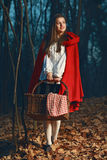 Smiling Little Red riding hood in the forest at night. Fairy tale and fantasy Stock Image