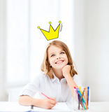 Smiling little school girl drawing at home Stock Image