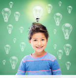 Smiling little school girl over light bulbs. Education, energy saving, children and people concept - smiling little girl over green chalk board background and Stock Photos