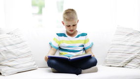 Smiling little schoolboy reading book at home Royalty Free Stock Photos
