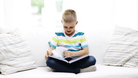 Smiling little schoolboy reading book at home Stock Image