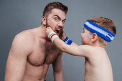 Smiling little son playing with dad beard Royalty Free Stock Images