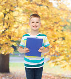 Smiling little student boy with blue book Royalty Free Stock Image