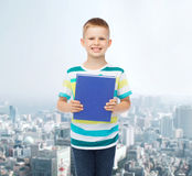 Smiling little student boy with blue book Stock Images