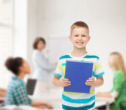Smiling little student boy with blue book Royalty Free Stock Images
