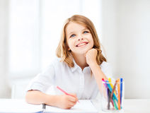 Smiling little student girl drawing at school Stock Images