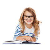 Smiling little student girl lying on the floor. Education and school concept - smiling little student girl with book and eyeglasses lying on the floor Royalty Free Stock Photos