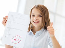 Smiling little student girl with test and A grade. Education and school concept - little student girl with test and A grade at school showing thumbs up Stock Photo