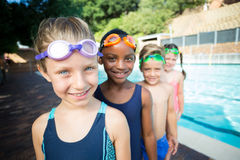 Smiling little swimmers standing at poolside. Portrait of smiling little swimmers standing at poolside Royalty Free Stock Image