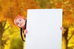 Smiling little young girl child in autumn clothes jacket coat and hat holding a blank billboard banner white board. Stock Photography
