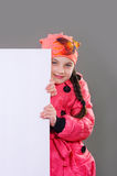 Smiling little young girl child in autumn winter clothes jacket coat and hat holding a blank billboard banner white board. Stock Photos