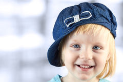 Smiling  llittle girl   with a cap on her head on a blue  background Stock Image