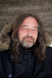 Smiling Long Hair Adult Man Wearing Hooded Jacket. Close up Happy Adult Man with Long Hair Wearing Black Fur Lined Hooded Jacket, Looking at the Camera Stock Photo
