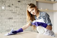Smiling long-haired blond woman cleaning table at home Stock Photography